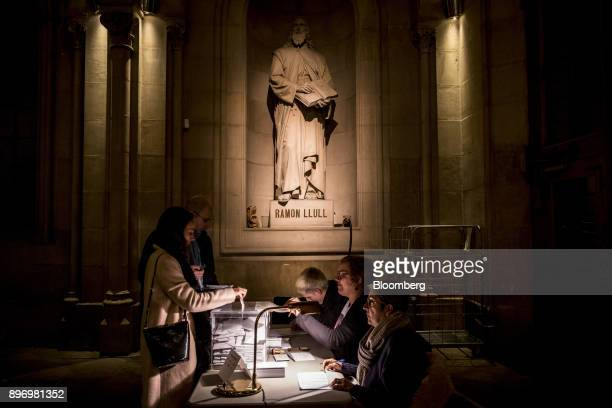 Voters drop their ballot papers into a box shortly before the polls close at the University of Barcelona in Barcelona Spain on Thursday Dec 21 2017...
