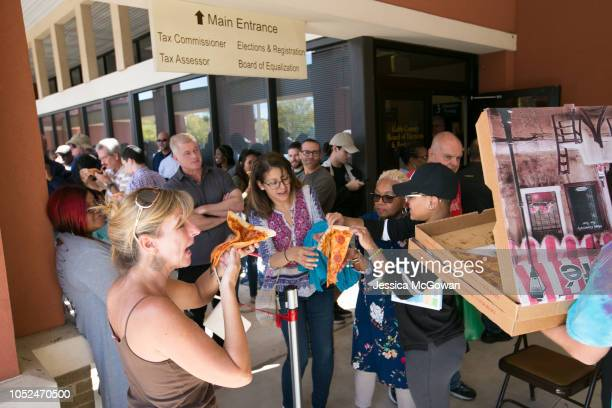 Voters enjoy a slice of donated pizza while waiting in line for up to two hours to early vote at the Cobb County West Park Government Center on...