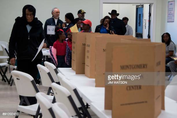 Voters file in to vote after standing in a long line that leads out the doors of the Beulah Baptist Church polling station in Montgomery AL on...