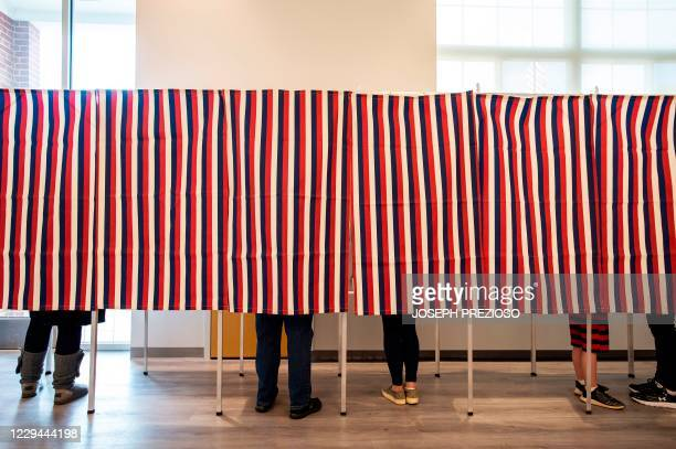 Voters fill in their ballots at polling booths in Concord, New Hampshire, on November 3, 2020. - Americans were voting on Tuesday under the shadow of...