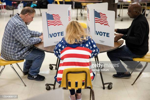 Voters fill in their ballots for the Democratic presidential primary election at a polling place in Armstrong Elementary School on Super Tuesday,...