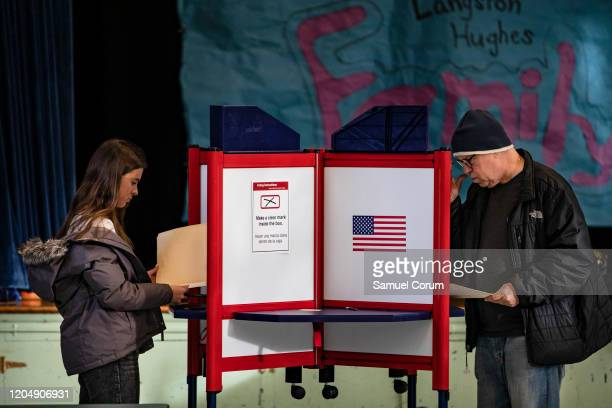 Voters fill in their ballots with their choice in the Democratic presidential primary elections at the Taylor Elementary School polling location on...