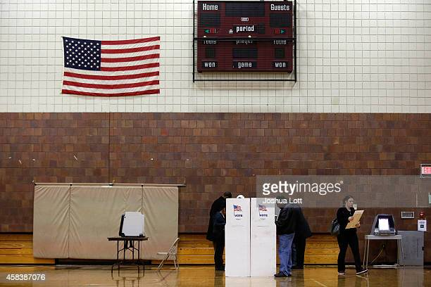Voters fill out their ballot at a polling station during the midterm elections November 4 2014 in Hamtramck Michigan Today Americans head to the...