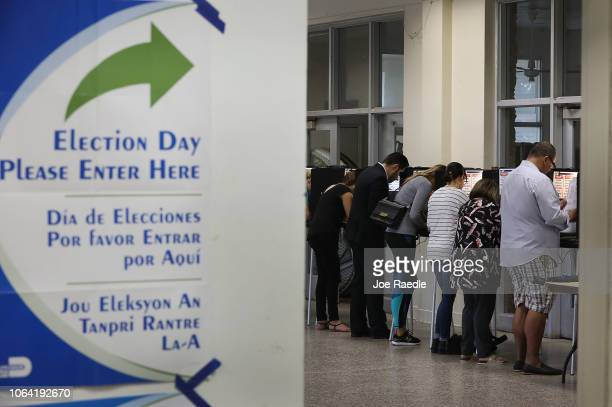 Voters fill out their ballots as they cast their vote at a polling station setup in Legion Park for the midterm election on November 06 2018 in Miami...