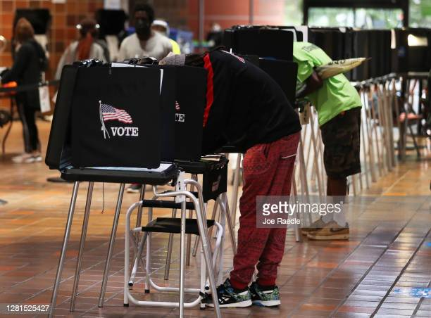 Voters fill out their ballots as they vote at the Stephen P. Clark Government Center polling station on October 21, 2020 in Miami, Florida. The state...