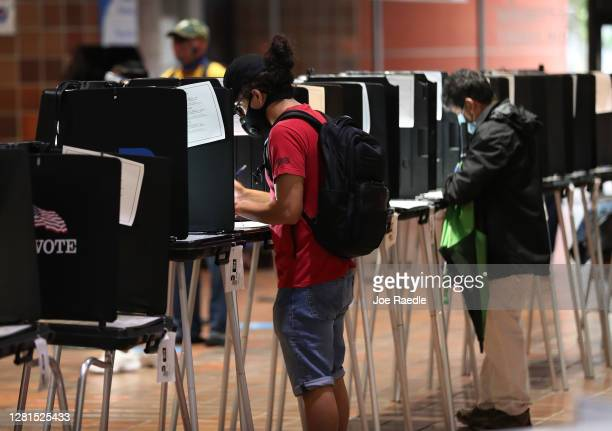 Voters fill out their ballots as they vote at the Stephen P Clark Government Center polling station on October 21 2020 in Miami Florida The state of...
