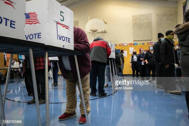 Voters fill out their ballots at a school gymnasium on November 03, 2020 in Lansing, Michigan. After a record-breaking early voting turnout,...