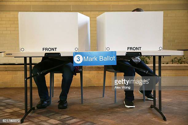 Voters fill out their paper ballots in a polling place on Election Day November 8 2016 in Arlington Virginia Americans across the nation pick their...