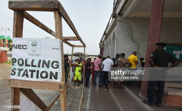 Voters form a queue at a polling station in Port Harcourt Rivers State on March 9 as voting has started to elect governors and lawmakers in 29 of the...