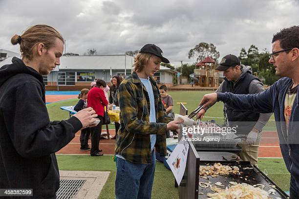 Voters have a sausage or snag in bread after casting their vote on election day to determine all 226 members of the 45th Parliament of Australia in...