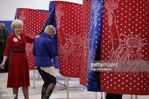 Voters head to the polling booths inside the Webster School gymnasium February 9 2016 in Manchester New Hampshire Tuesday is the 100th anniversary of...