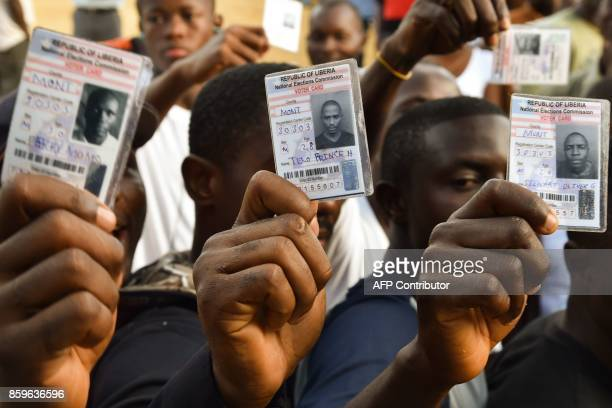 Voters hold their voting card prior to casting their vote for Liberia's presidential and legislatives elections at a polling station in Monrovia on...