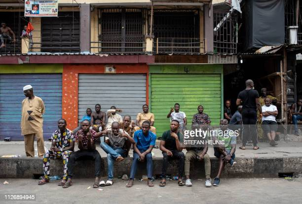 Voters in Balogun Market sit on the sidewalk at one of the polling units in Lagos while votes are counted during the presidential and parliamentary...