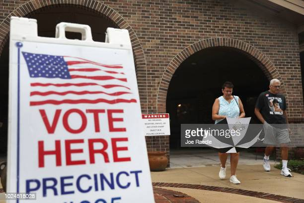 Voters leave after casting their votes at a polling station for the state primary elections on August 28 2018 in St Augustine Florida Republican Gov...