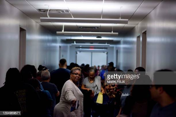 Voters line up at a polling station to cast their ballots during the presidential primary in Houston Texas on Super Tuesday March 3 2020 Fourteen...
