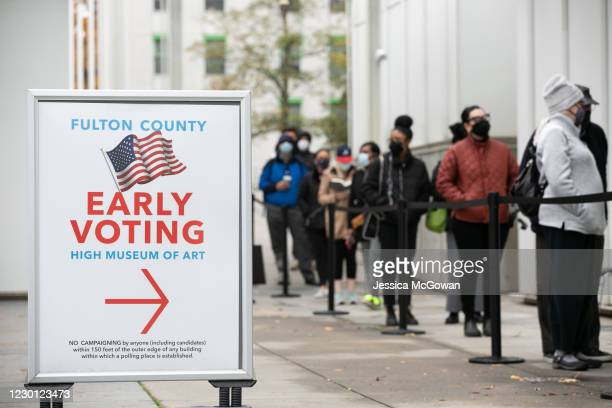 Voters line up for the first day of early voting outside of the High Museum polling station on December 14, 2020 in Atlanta, Georgia. Georgians are...