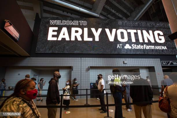 Voters line up inside of State Farm Arena, Georgia's largest early voting location, for the first day of early voting in the general election on...