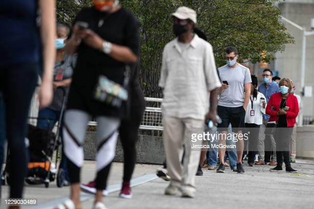 Voters line up outside of State Farm Arena, Georgia's largest early voting location, for the first day of early voting in the general election on...