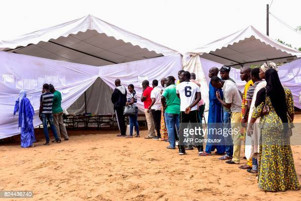 TOPSHOT Voters line up prior to casting their vote in Senegal's legislative election on July 30 2017 in Dakar Senegalese voters cast ballots on July...