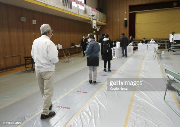 Voters line up to cast ballots while maintaining social distancing to prevent coronavirus infection in Osaka on Nov. 1 as a referendum is held on a...