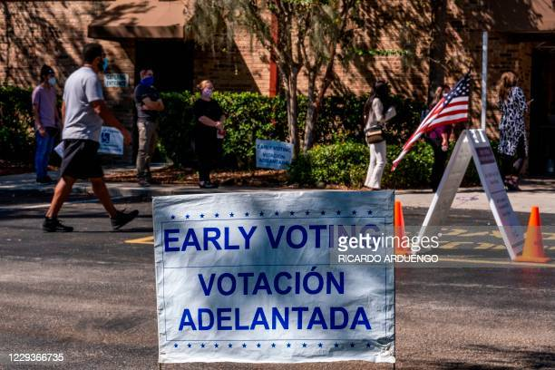 Voters line-up to cast their ballots during early voting at the Kissimmee Civic Center in Kissimmee, Florida, on October 30, 2020. - Trump and Biden...