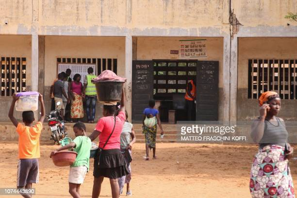 Voters look at an electoral list as people walk past them outside a polling station in the Tokoin neighbourhood in Lome on December 20 2018 during...