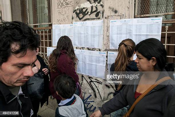 Voters look at polling sheets posted outside of a polling station during the presidential election in Buenos Aires Argentina on Sunday Oct 25 2015...