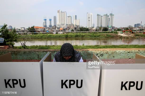 Voters mark their ballots at a polling centre during elections in Jakarta Indonesia on April 17 2019 Indonesia's general elections pitting incumbent...