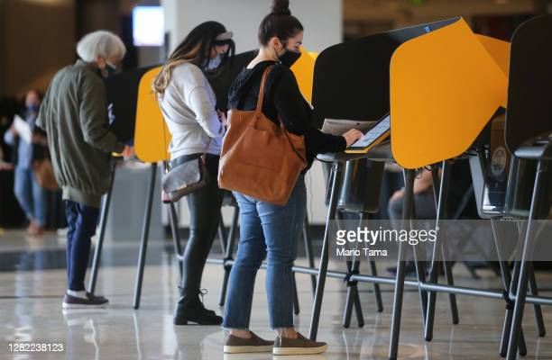 Voters mark their ballots at a Vote Center located at the Staples Center on the first weekend of early in-person voting on October 25, 2020 in Los...