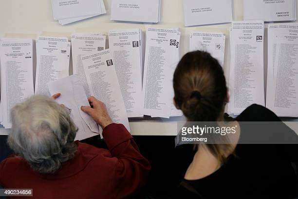 Voters pick up their ballot papers from a table in a public school used as a polling station during the Catalonian parliamentary election in...