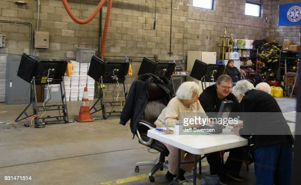 Voters place their ballots in a special election between Democratic candidate Conor Lamb and Republican candidate Rick Saccone March 13 2018 at the...