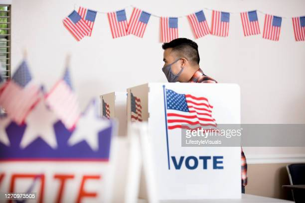voters placing their ballots.  wearing face masks. - election voting stock pictures, royalty-free photos & images