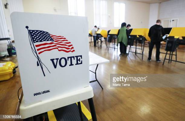 Voters prepare their ballots in voting booths during early voting for the California presidential primary election at an LA County 'vote center' on...