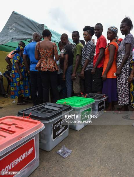 Voters queue at a polling station at Ubima Town on the outskirts of Port Harcourt Rivers State on March 9 during voting to elect governors and...