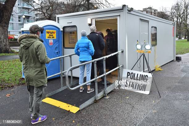 Voters queue at the entrance of a portacabin set up as a polling station in Brighton and Hove southeast England as Britain holds a general election...