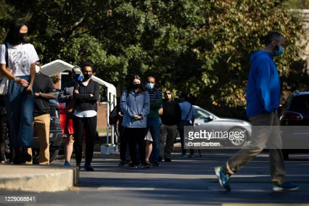 Voters queue outside of a library building to participate in early voting on October 14 2020 in Nashville Tennessee Early voting in Tennessee started...