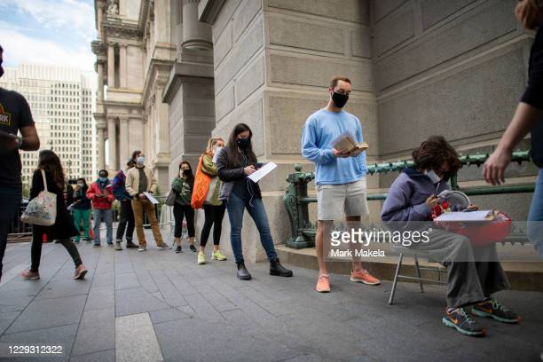 Voters queue outside of Philadelphia City Hall to cast their early voting ballots at the satellite polling station on October 27, 2020 in...