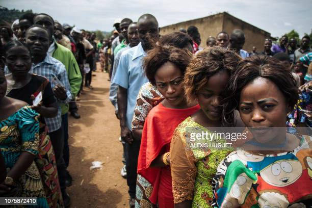Voters queue to cast their ballots at a symbolic polling station on December 30 at Malepe Stadium in Beni where voting was postponed for Democratic...