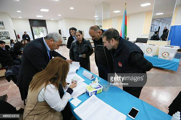 Voters receive their ballot papers at a polling station in Baku in Azerbaijan's parliamentary elections in central Baku
