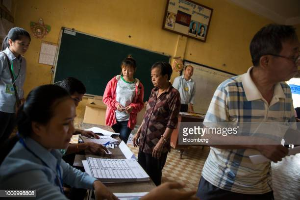 Voters register before casting their ballots for the general election at a polling station in Phnom Penh Cambodia on Sunday July 29 2018 As...