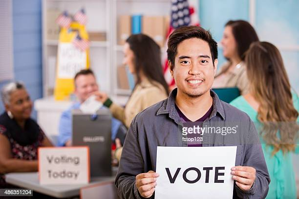 Voters register, vote USA elections. Asian man holds 'Vote' sign.