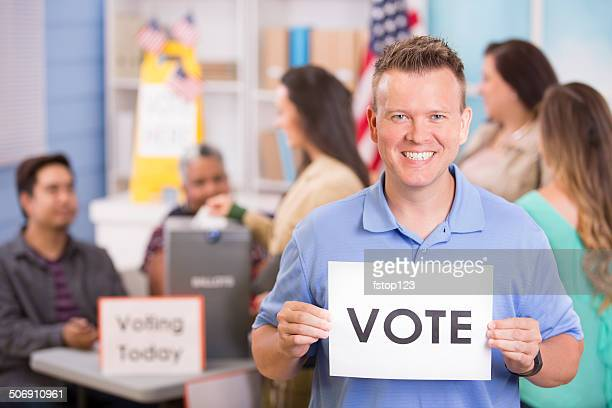 Voters register, voting in USA elections. Man holds 'Vote' sign.