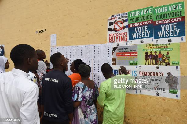 Voters search for their details on a list taped up on a wall during the Osun State gubernatorial election in Ede in the Osun State in southwest...