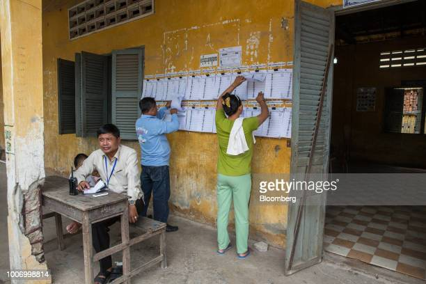 Voters search for their names on voters lists at a polling station before casting their ballots for the general election in Phnom Penh Cambodia on...