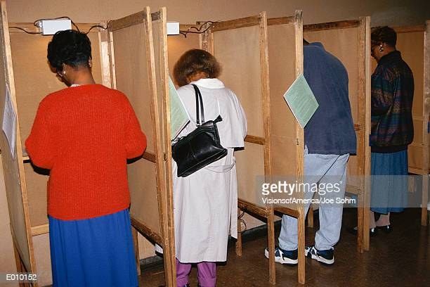 Voters selecting candidates in voting booths