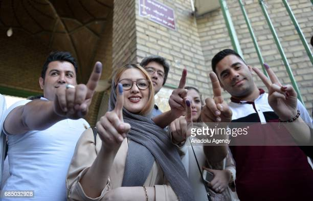 Voters show their inkstained fingers after casting their ballots during Iran's 12th presidential election at Irshad Mosque in ShahreRay county of...