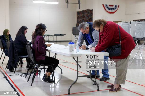 Voters sign in before casting their ballots at the Fitzgerald Recreation Center on March 10, 2020 in Warren, Michigan. Michigan is one of six states...