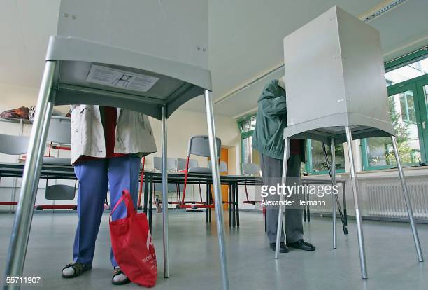 Voters stand in a polling booth in a polling station voting in the German Bundestag elections on September 18 2005 in Gross Gerau Germany