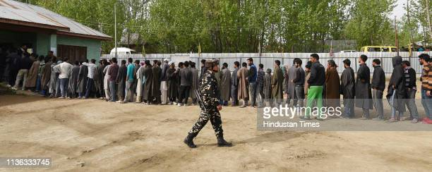 Voters stand in a queue to cast their votes outside a polling station at Dangerpora on April 11 2019 in Bandipora district some 30 Kms from Srinagar...