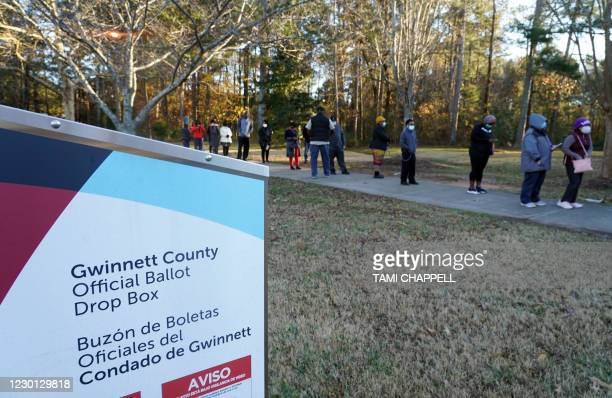 Voters stand in line to cast their ballots during the first day of early voting in the US Senate runoffs at Lenora Park, December 14 in Atlanta,...